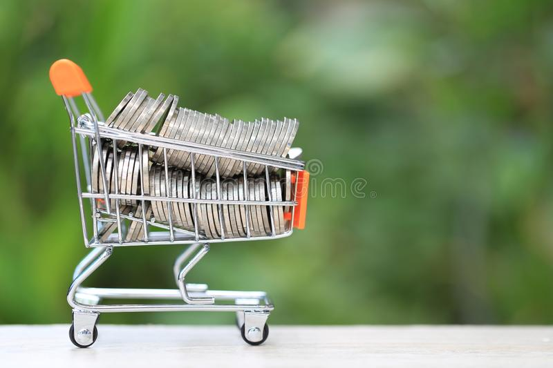 Finance, Stack of gold coins money in mini shopping cart on natural green background, Business investment growth and Save money. For prepare in future concept stock images