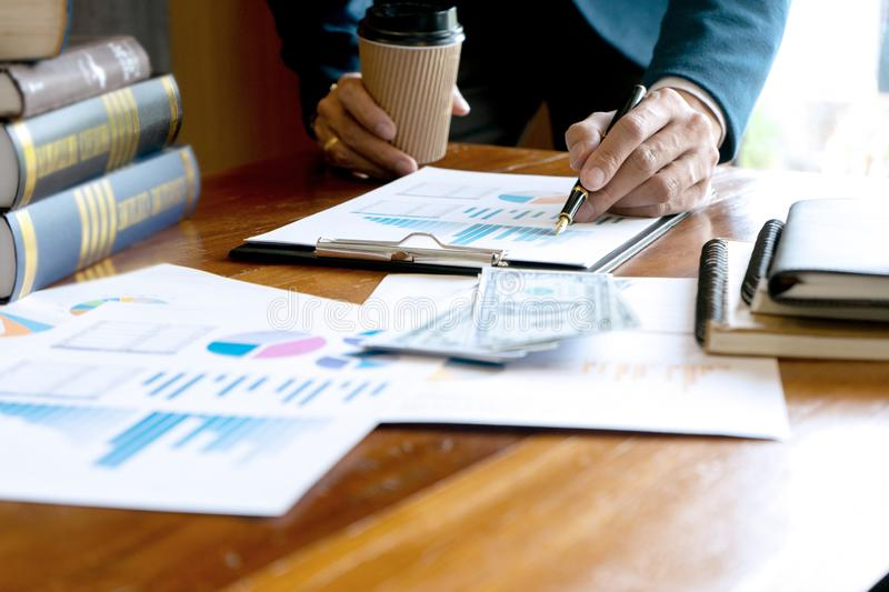 Finances and accounting business  concept. On the table, Businessman pointing at graph and chart to data analysis use for plans  improve quality, finances and stock photo