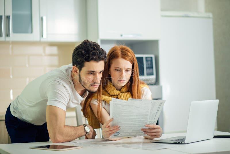 Finances de gestion de couples, passant en revue des comptes bancaires utilisant l'ordinateur portable photos stock