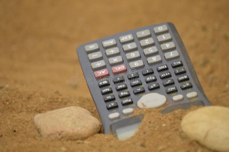 Finances in difficult times. Electronic Calculator in hostile environment, arid, desolate, dry and sandy. Losing your mind in adverse contrary, stressful, tough royalty free stock image