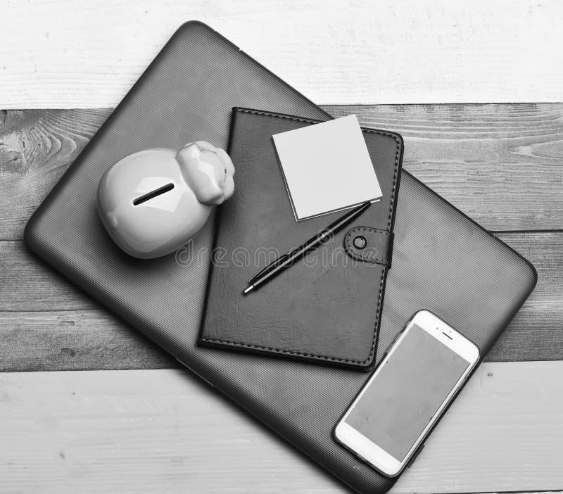 Finances et concept de budget Composition en siège social Tirelire près d'organisateur, stylo, notes collantes, téléphone image stock