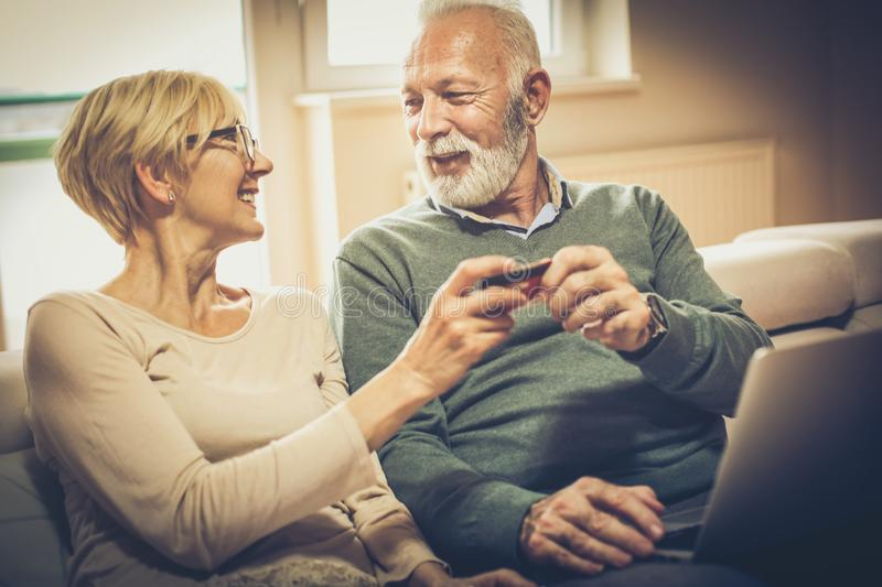 Finances are good for us. Senior couple at home checking finance on credit card royalty free stock photos