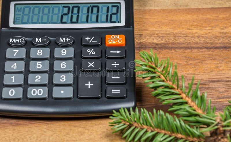 Financez la calculatrice avec le nombre de nouvelle année sur l'affichage et la branche d'arbre impeccable Fin vers le haut photos libres de droits