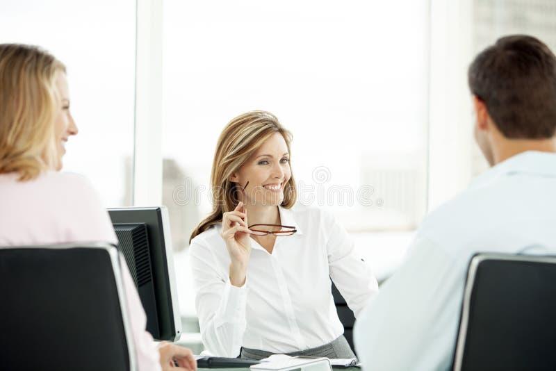 Financiële adviseur met paar op vergadering in bureau - advocaat die advies geven aan de mens en vrouw - makelaar in onroerend go royalty-vrije stock foto