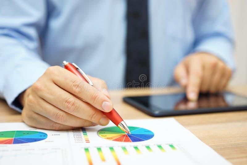 Financiële arbeider die bedrijfsgegevens analyseren en met tablet werken stock afbeeldingen