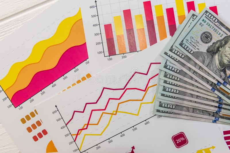 Financiële diagrammen en dollarbiljetten sluiten dicht stock foto's