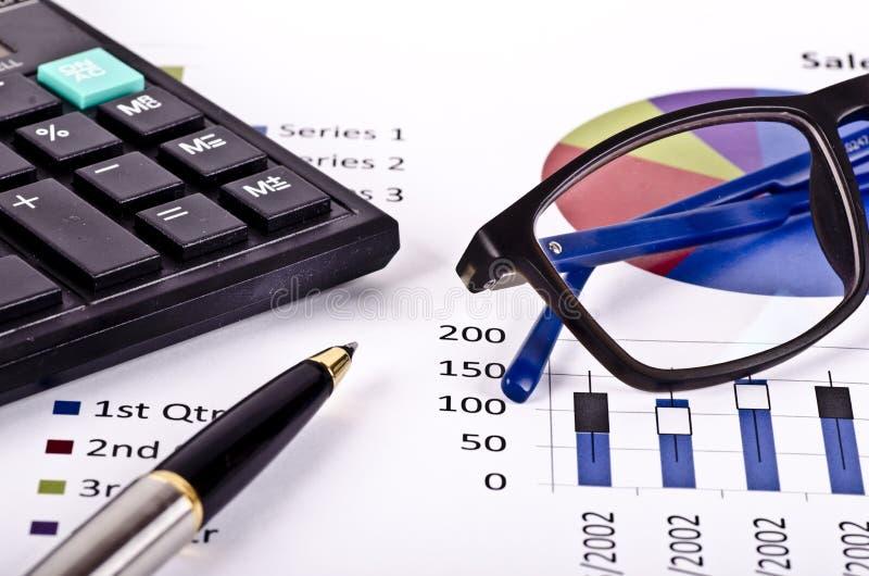 Financiële hulpmiddelen, calculator, pen en bril over een rapport royalty-vrije stock foto's