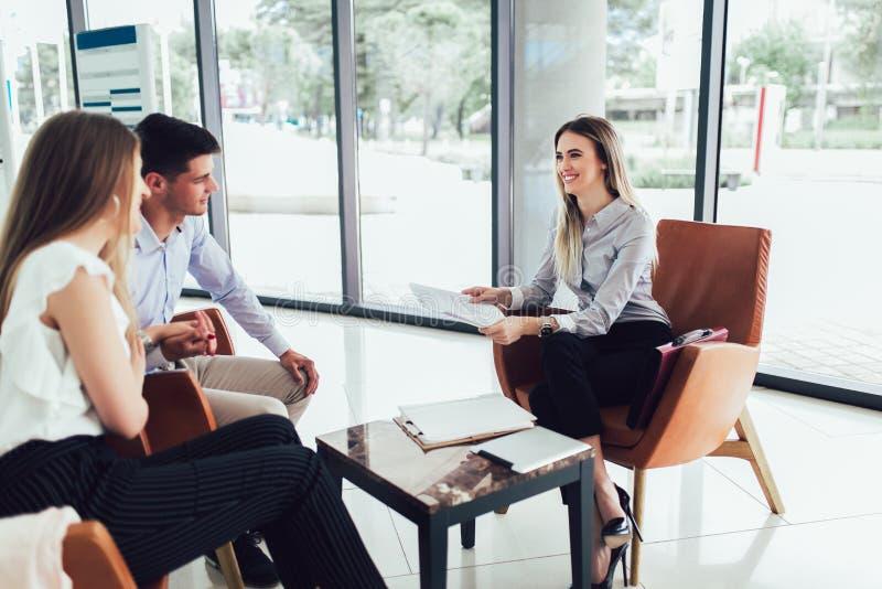 Financi?le adviseur die rapport tonen aan jong paar voor hun investering Verkoper en positief paar die over aankoop spreken royalty-vrije stock afbeelding
