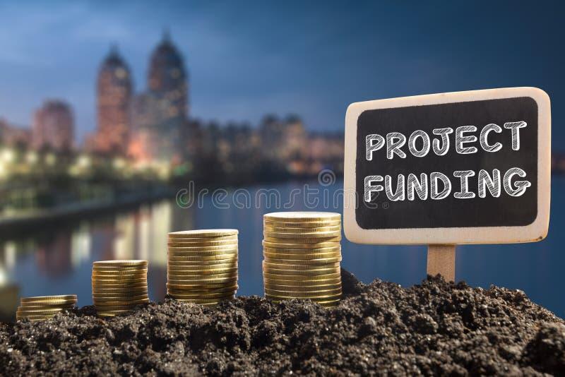 Financiación de proyecto Concepto financiero de la oportunidad, del negocio y del intertnet Monedas de oro en pizarra del suelo e foto de archivo