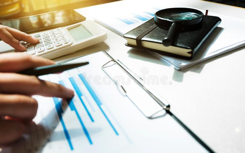Financial accounting Business woman using calculator while pointing on data documents stock photos