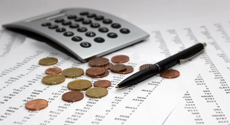 Financial accounting, Image a plurality of numbers on paper and calculator, coins. Financial accounting, Image a plurality of numbers on paper and calculator royalty free stock images