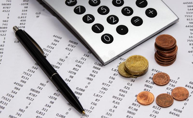 Financial accounting, Image a plurality of numbers on paper and calculator, coins. Financial accounting, Image a plurality of numbers on paper and calculator stock photo