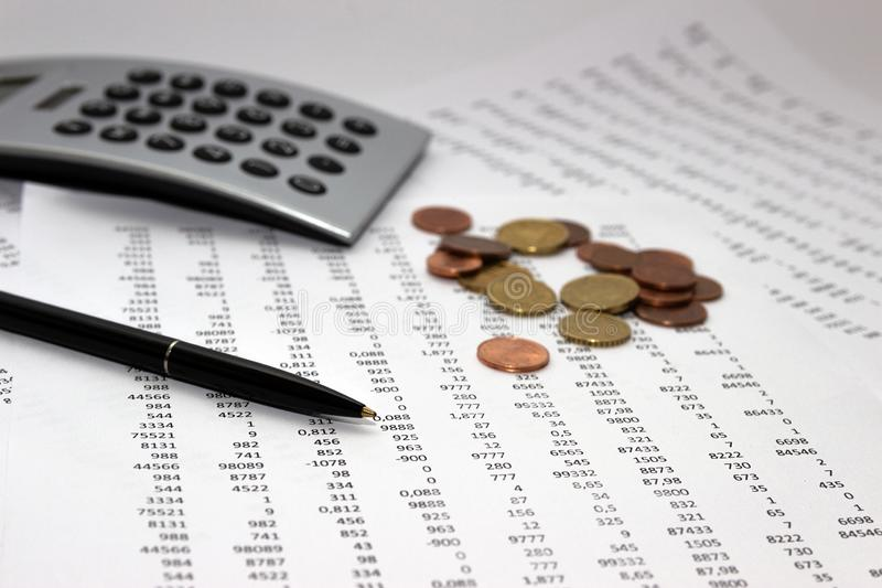 Financial accounting, Image a plurality of numbers on paper and calculator, coins. Financial accounting, Image a plurality of numbers on paper and calculator royalty free stock image