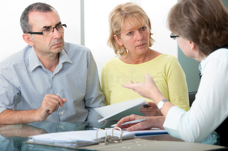 Financial advice. Couple getting financial advice from consultant at home royalty free stock photography