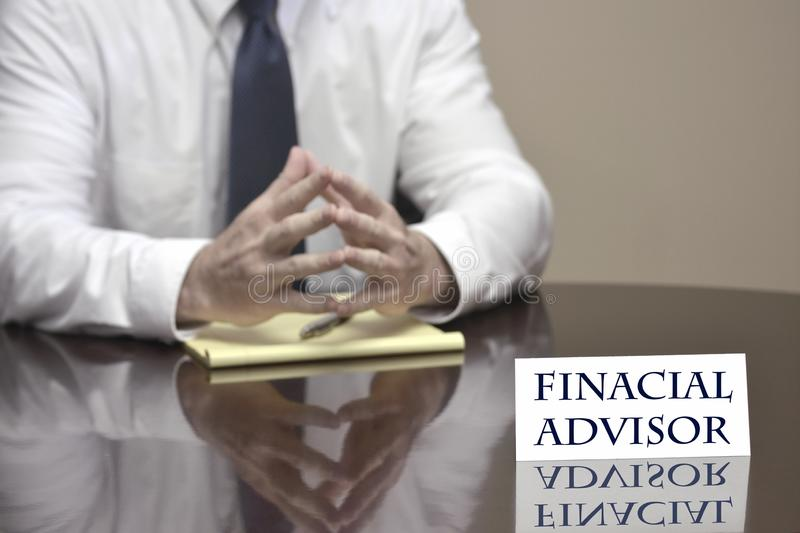 Financial Advisor Business Man Businessman Helping with Finances. Financial advisor man business businessman at desk with sign helping finances royalty free stock image