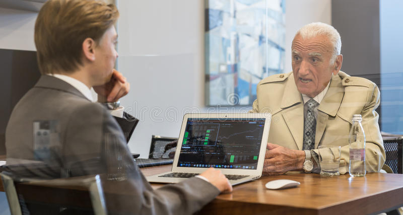 Financial advisor consulting senior client with his investment strategy. Young financial advisor sitting in front of laptop, consulting senior client with his royalty free stock photos