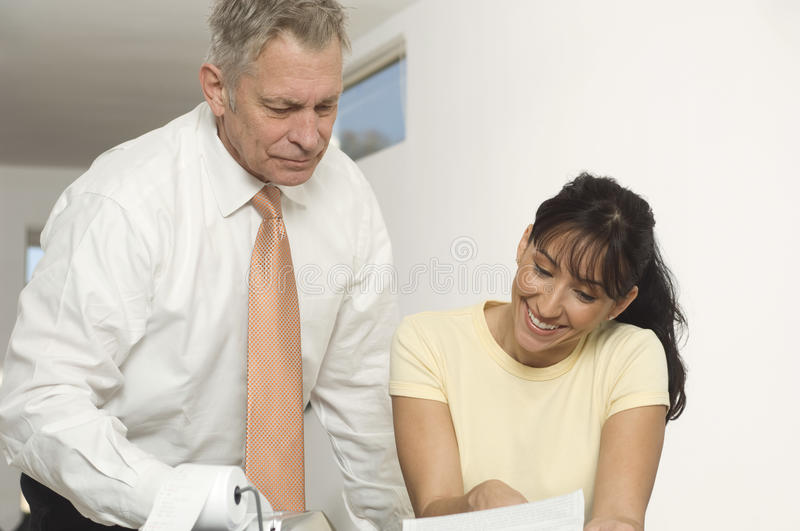 Financial Advisor In Discussion With Woman. Senior advisor in discussion with happy women over financial documents stock photo