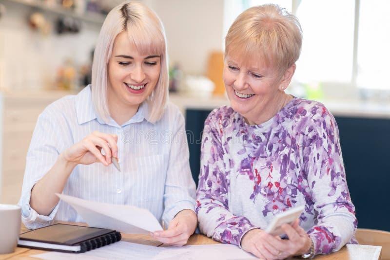 Financial Advisor Helping Senior Neighbor With Paperwork stock images