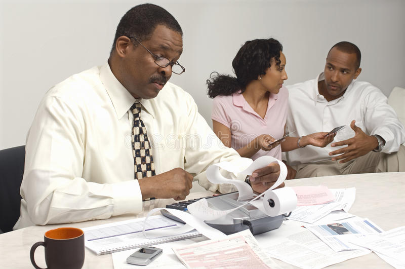 Download Financial Advisor Holding Expense Receipt With Couple In The Background Stock Photo - Image: 29661230