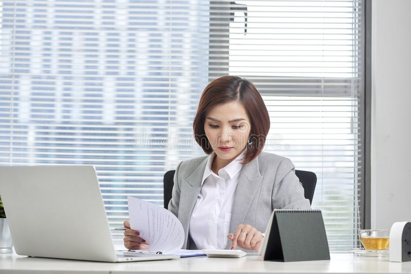 Financial advisor using calculator review financial statement on desk. Accounting concept stock images
