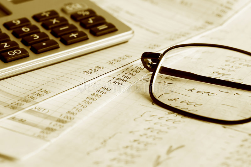 Financial analysis. Glasses and calculator on the business papers royalty free stock image