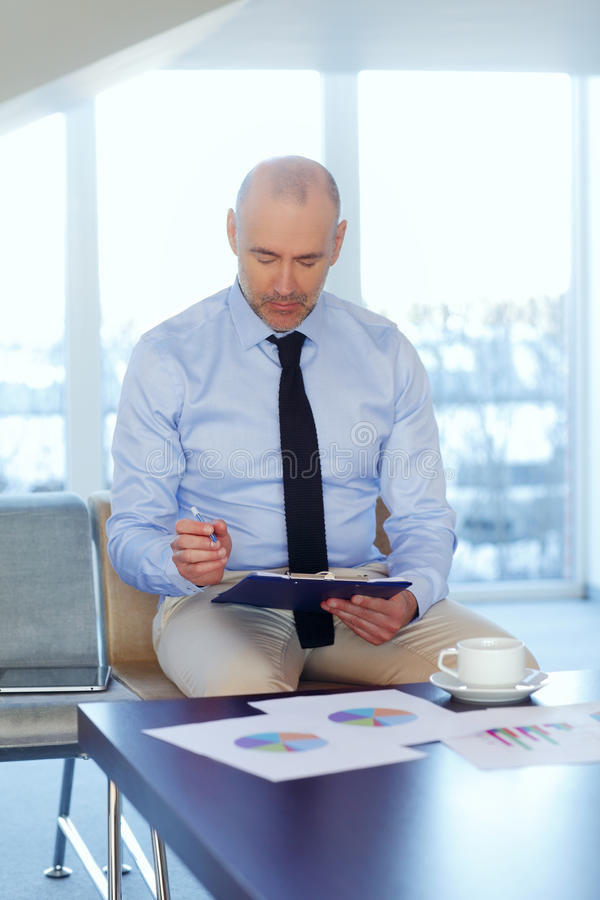 Financial analyst portrait. Portrait of financial analyst sitting at desk and analyzing financial data. Businessman holding hands clipboard stock image