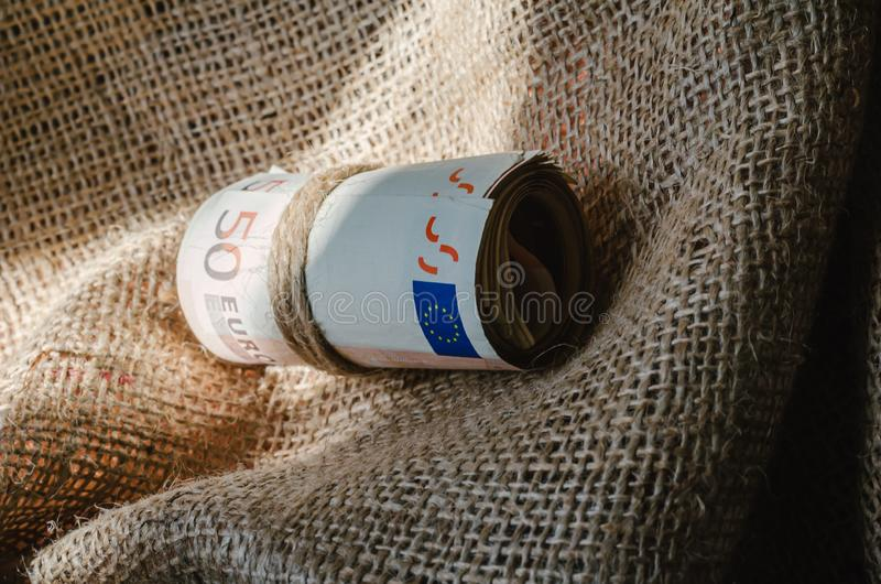 Financial assistance to parents living in the village from children. Banknotes twisted and tied with twine on burlap. Caring for your parents. Close-up royalty free stock image