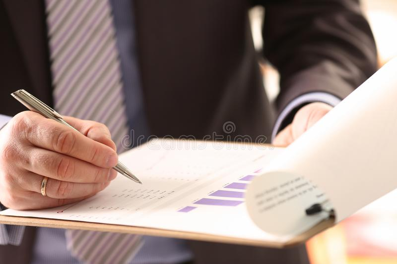 Financial Auditor Signing Calculating Document. Consulting Business Man. Profit Accounting with Color Graph. Audit Inspection and Calculating Investment stock photography