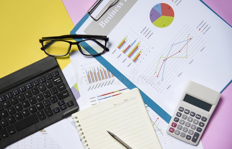 Financial and business graph chart report paper document with calculator open notebook paper stock image