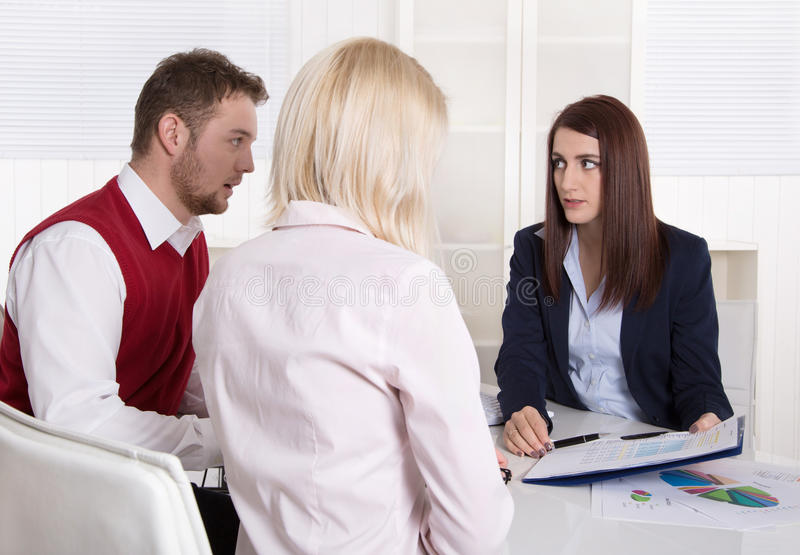 Financial business meeting: young married couple - adviser and c. Lients sitting at desk stock images