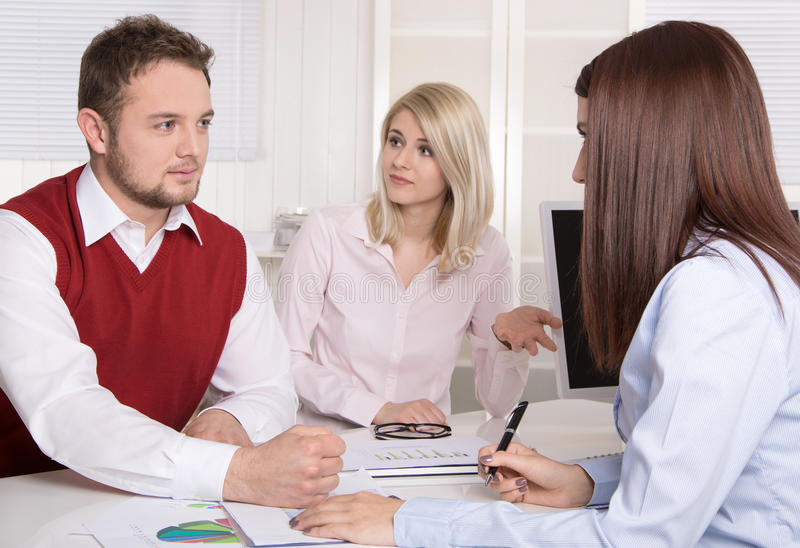 Financial business meeting: young married couple - adviser and c. Lients sitting at desk royalty free stock photo