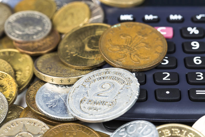 Financial concept. Calculator surrounded by various world currency coins closeup.  royalty free stock image