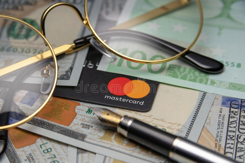 Financial concept. glasses and a mastercard card are on dollars. Cheboksary, Russia, 11/25/2018. Financial concept.. glasses and a mastercard card are on dollars stock photo