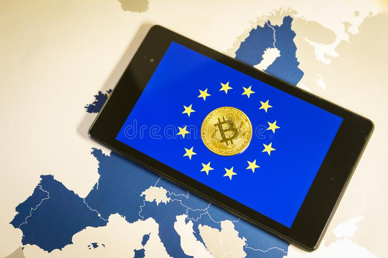 Financial concept with golden Bitcoin over smartphone, EU flag and map. royalty free stock photography