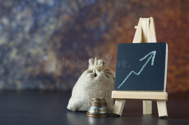 Financial concept. Money bag and up drawn chart. Increase of salary or income. Copy space, dark background. Financial concept. Money bag and up drawn chart royalty free stock image