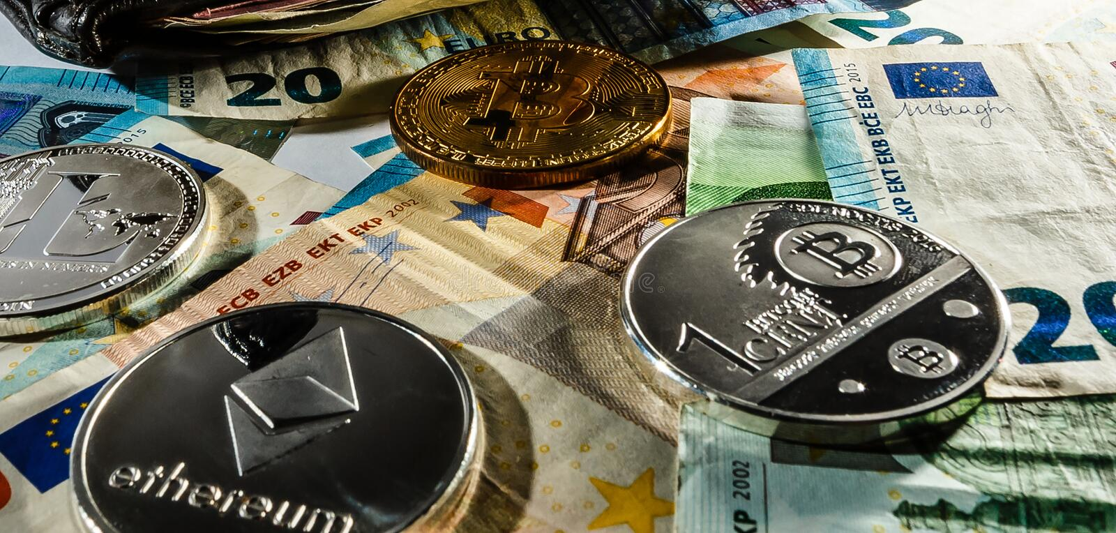 Financial concept with physical bitcoin and ethereum over a leather wallet with euro bills inside stock photography