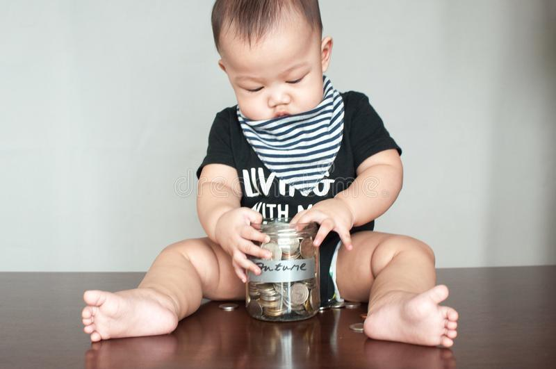 A baby boy is holding a jar filled with coins. A financial concept wherein a baby boy is holding a jar filled with coins royalty free stock images
