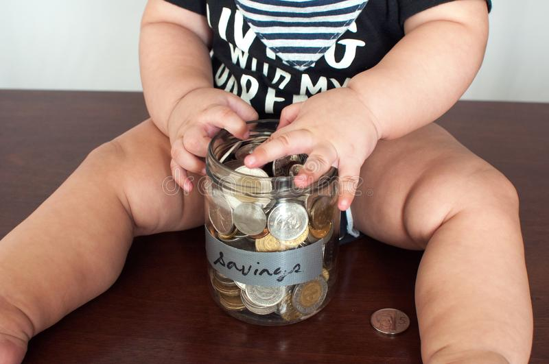 A baby boy is holding a jar filled with coins royalty free stock photography