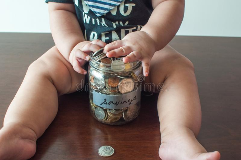 A baby boy is holding a jar filled with coins royalty free stock photos