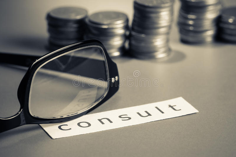 Financial consult. Ant, eyeglasses and coins with paper of consult word royalty free stock photos