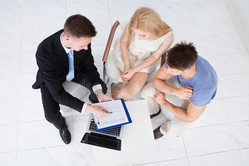 Financial consultant presenting new project investment to couple royalty free stock photography
