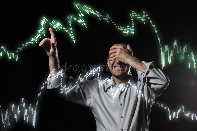 Financial crisis. Scared trader pointing stock market charts royalty free stock photography