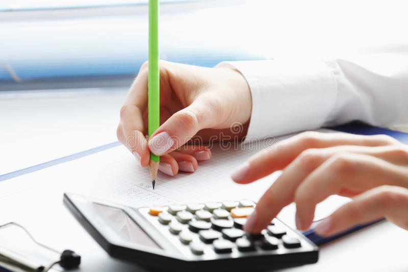 Financial data analyzing. Counting on calculator. Financial data analyzing. Close-up photo of a businesswoman's hand writing and counting on calculator in royalty free stock photo