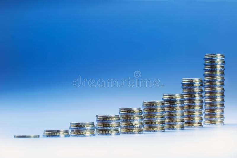 Financial diagram - the graph of economic growth. Euro coins stacked in columns in order from smallest to largest. Blue background stock photography