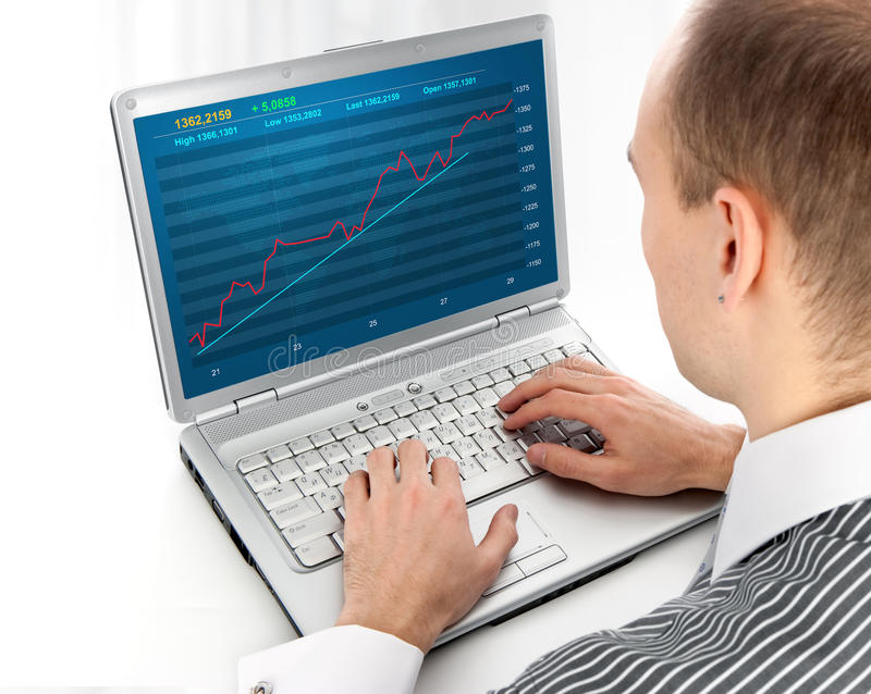 Financial diagram on a monitor. Young man working of a laptop with Financial diagram stock photo