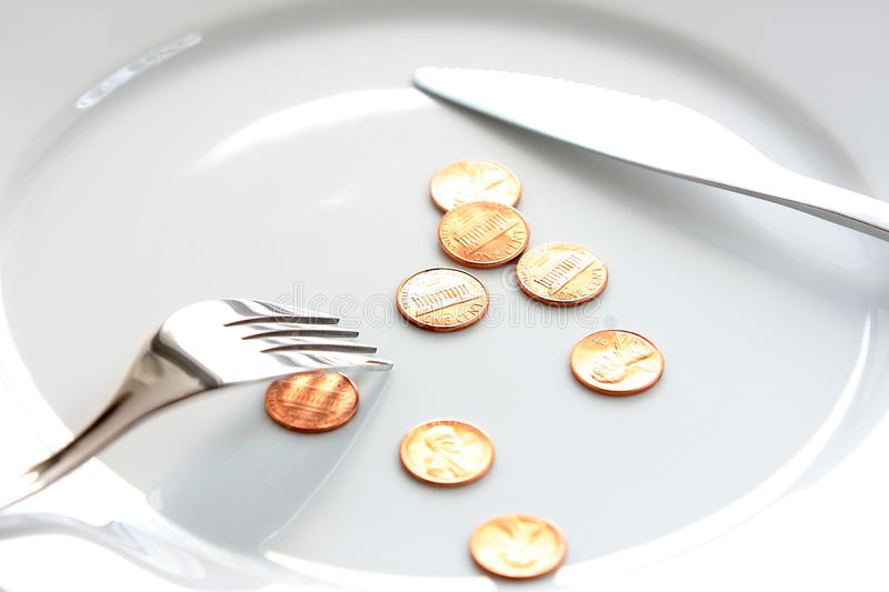Financial difficulty. A few coins of one american cent on a white plate, with fork and knife. Financial difficulty, cost of living, savings, donations & other stock photo