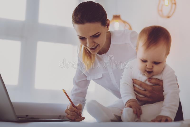 Financial director on maternity leave correcting her business data. Data corrections. Financial director on maternity leave feeling occupied while correcting her royalty free stock image