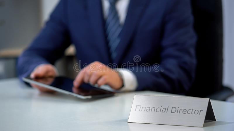 Financial director in suit scrolling on tablet pc, watching corporative files. Stock photo royalty free stock images