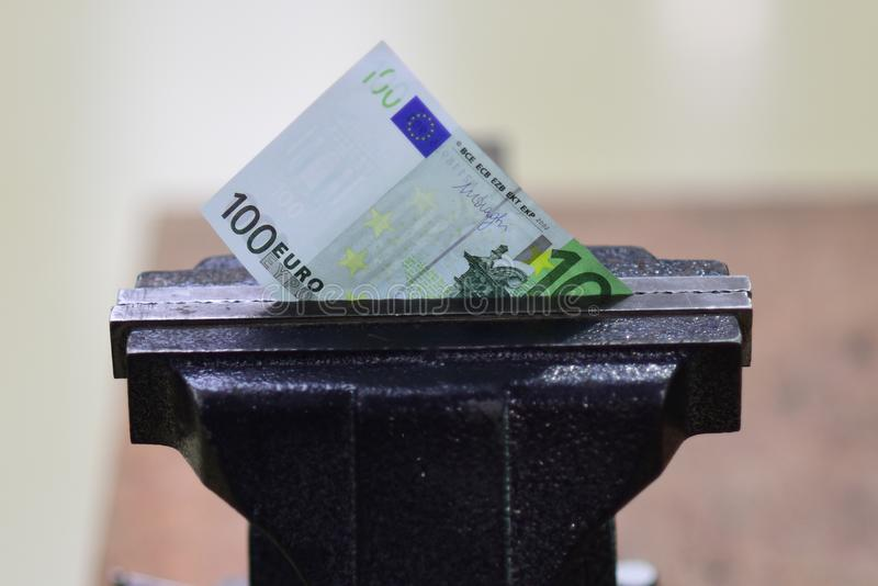 Financial or economic metaphor, euro bill in clamp royalty free stock photography
