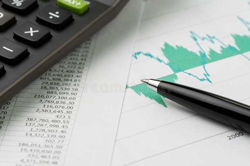 Financial equity, stock exchange price index, budget, economics. Or investment concept, pen on graph and chart print paper with calculator on price numbers royalty free stock photos